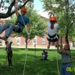 Chelsea Wallace and Snousha Glaude wait their turn while Brandon Haefke and Anna Spiers learn the ropes of tree climbing.